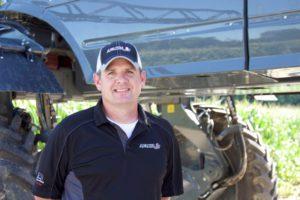 Adam Kivett in front of an Apache Sprayer