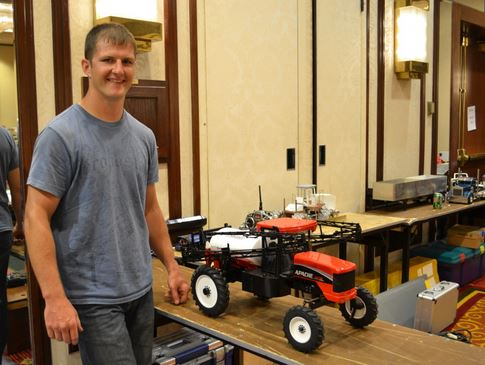 Nathan Rowings stands next to his remote control Apache sprayer